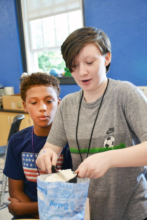 Eleanor Levi levels a cup of flour as Jaciyon Graves watches during a cooking class where students were making pancakes during Danville's STEAM camp on Wednesday.(Photo by Robin Hart)