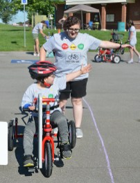 During the Kids Can Bike camp on Tuesday morning, Skylar Ward uses a left hand turn signal he had just learned as volunteer Matrie Harmon encourages him. Photo by Robin Hart)