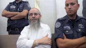 Ezra Sheinberg in court, flanked by police officers