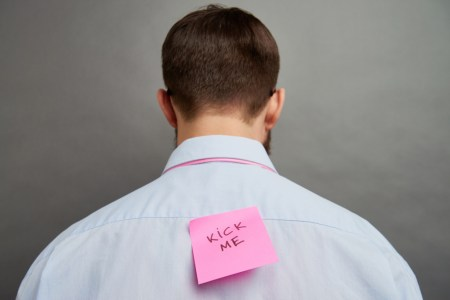 """Rear view of man with note on his back that says """"Kick Me"""""""