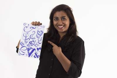 Uttara Valluri holds up her blue and white collage of Ampersands