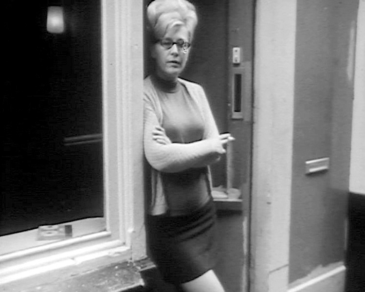Amsterdam's Red Light District in the 1960's. A prostitute stands in the doorway of a brothel.