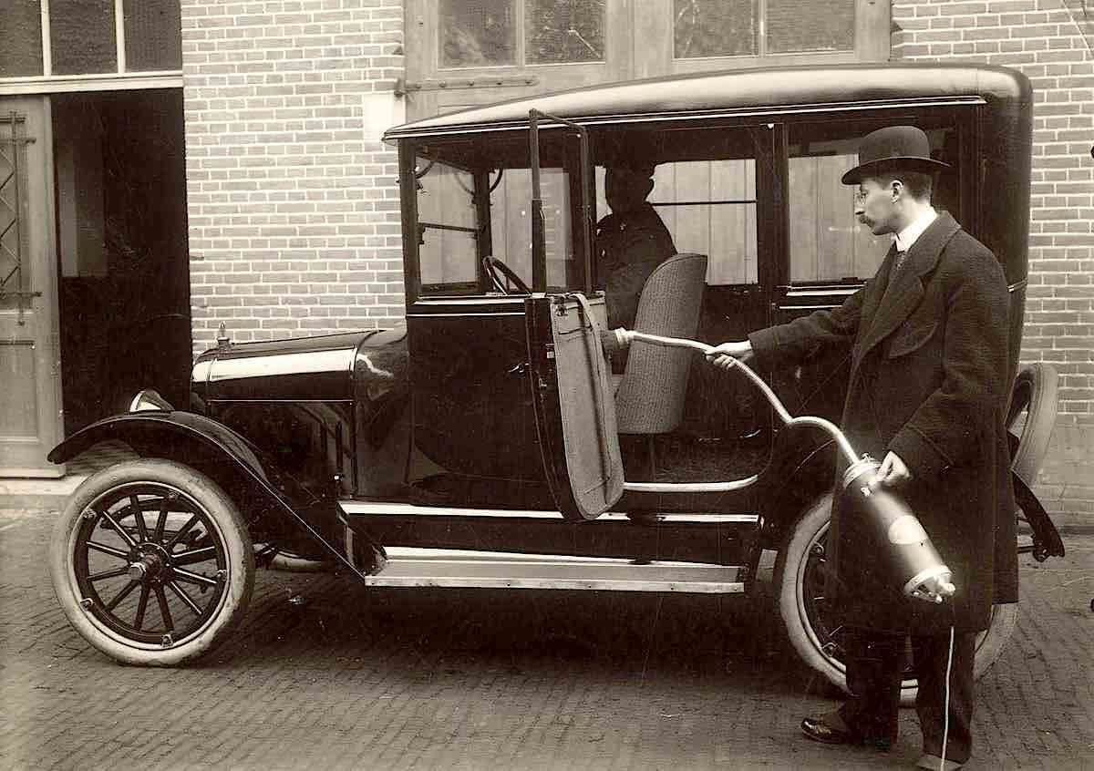 Holland, Amsterdam in 1916. A man cleans a car with a vacuum cleaner.