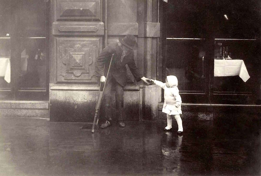 Amsterdam, Leidse Square, year 1916. Little girl gives money to scrounger