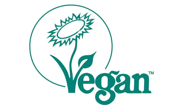 The Vegan Trademark from the Vegan Society. The word vegan appears in green with a flower and leaf sprouting out of the V.