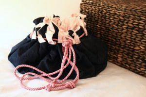 A toy sack (which lies flat as a baby mat) made from dark denim on the outside, a baby pink cotton fabric on the inside, and with a draw-cord of twisted rayon cord in blossom pink.