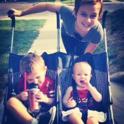 babysitter with little boy and girl in a stroller