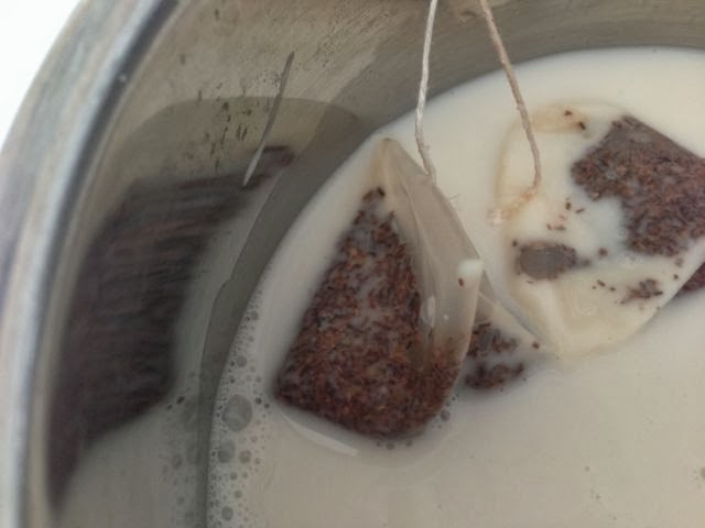 two teabags in milk in a pan