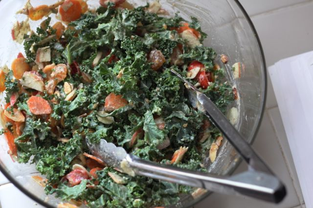 tossed kale salad with tongs