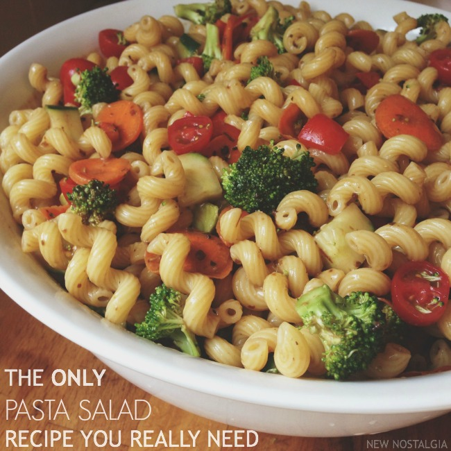 bowl of pasta salad with broccoli, carrots and tomoates