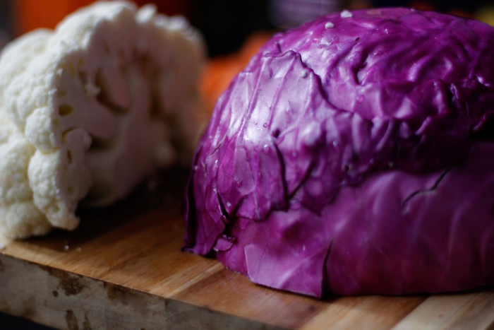 Head of cut cauliflower and a head of purple cabbage
