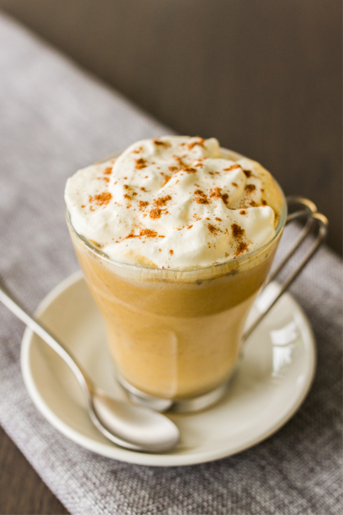 a glass mug of salted caramel pumpkin latte topped with whipped cream