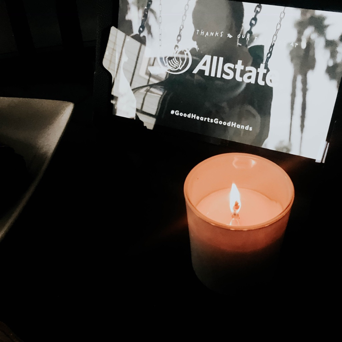 allstate video on a screen and a candle