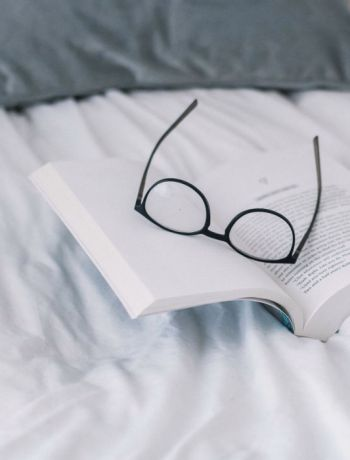 book and glasses on a white bedspread