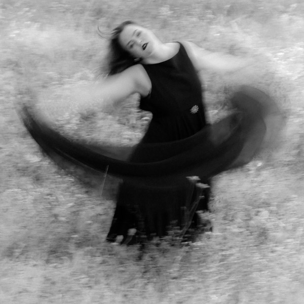 B & W Photographic image with a mystical feel of a woman in a black dress dancing with a black scarf in a field of white.