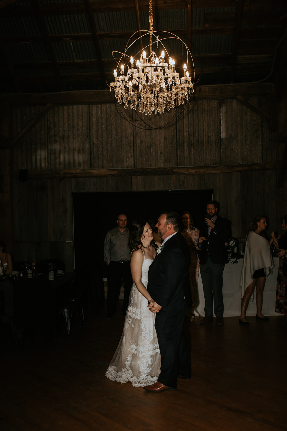 wedding couple dancing in a barn under a crystal chandelier