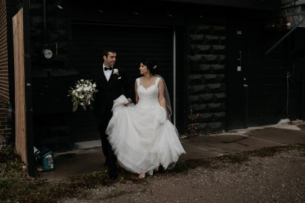 bride and groom walking in front of black wall