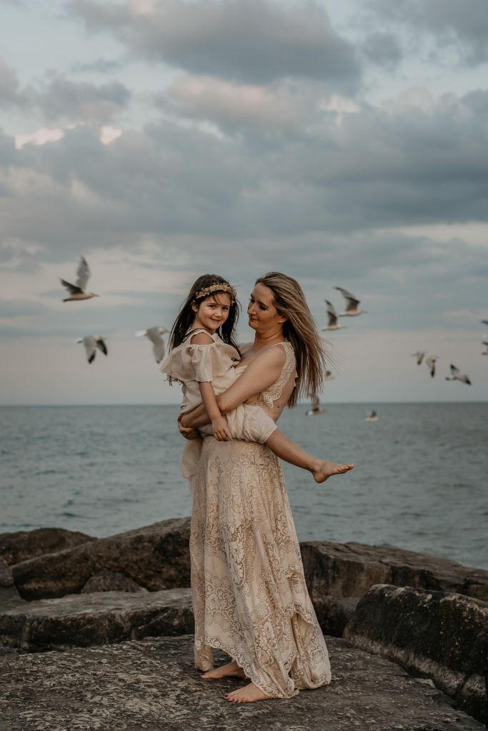 Mother and daughter family portrait at Toronto, Ontario beach with seagulls flying in background. Toronto Family Photographer