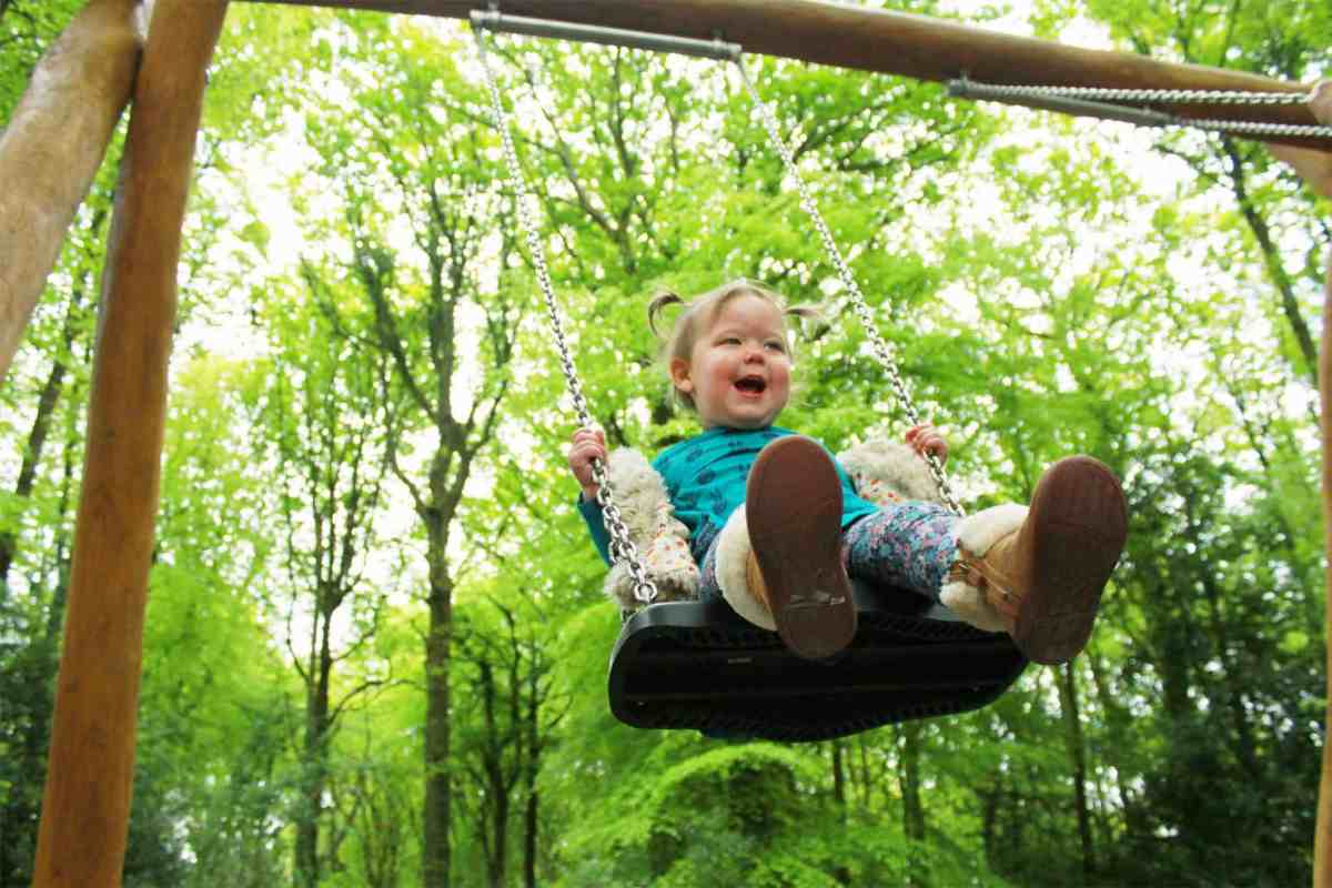 Little girl playing on swing in the middle of a woodland park
