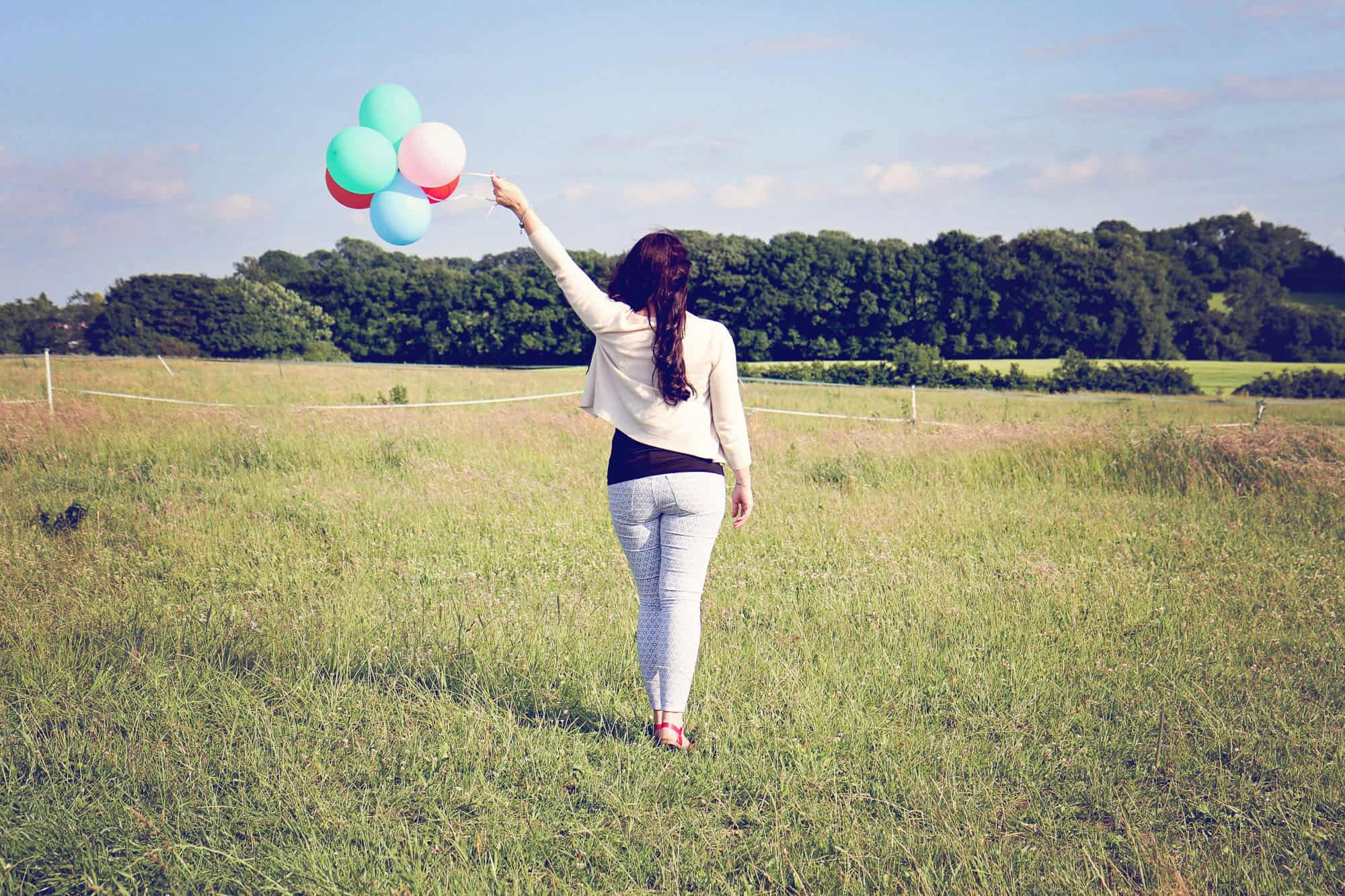 Woman standing in a field holding balloons