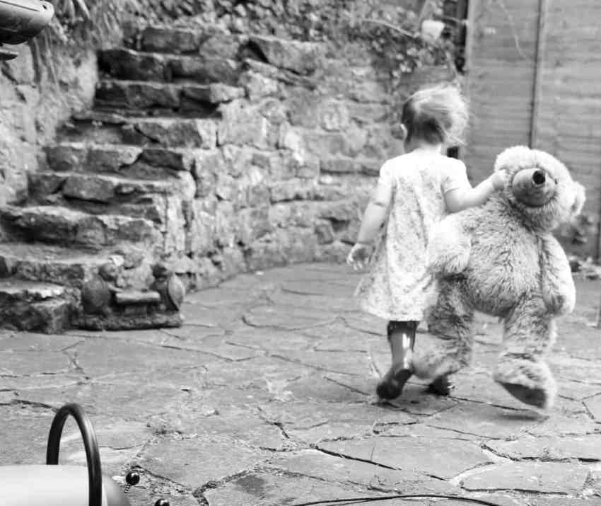 black and white photograph of a little girl with a giant teddy bear