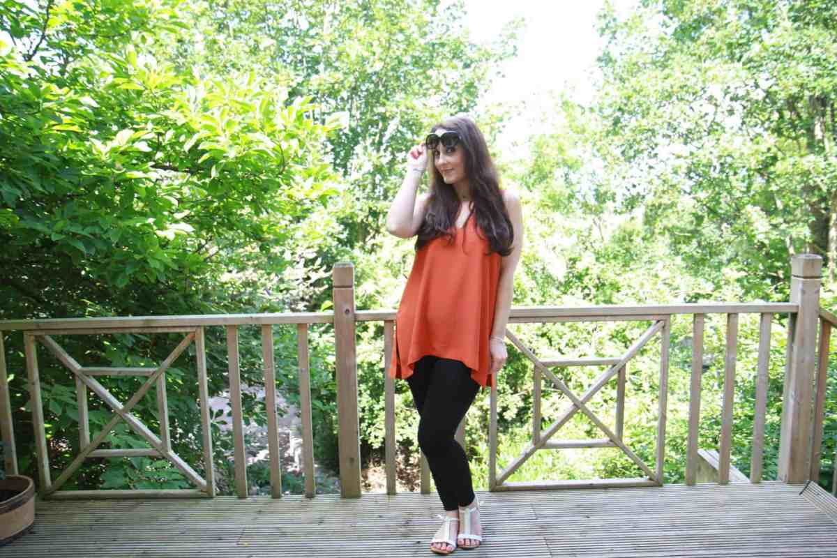 Casual daywear-toyshop tunic in burnt orange worn with black leggings, sandals and Bvlgari sunglasses