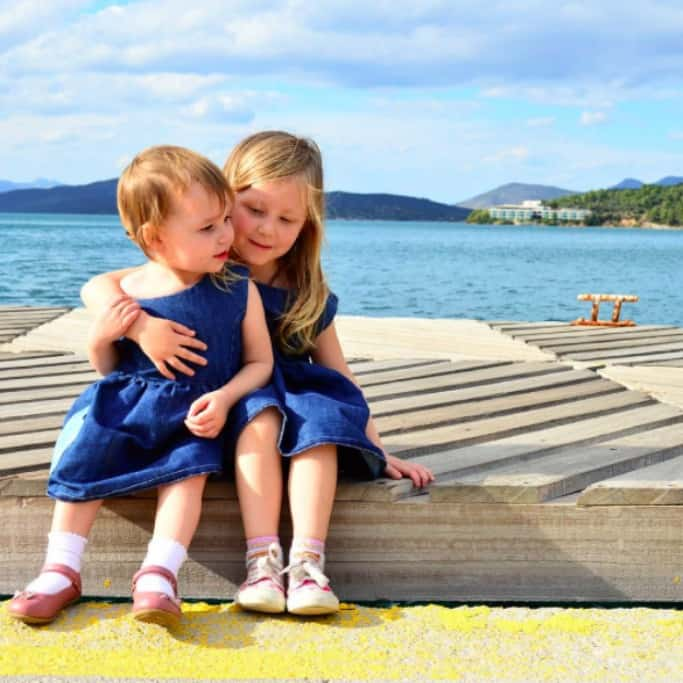 Two girls sitting beside the sea dressed in matching blue