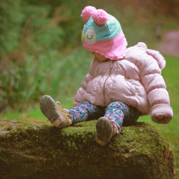 Little girl sitting on a tree trunk watching a squirrel