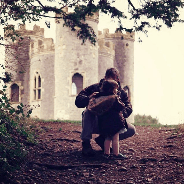 Little girl and her daddy in front of a fairytale castle