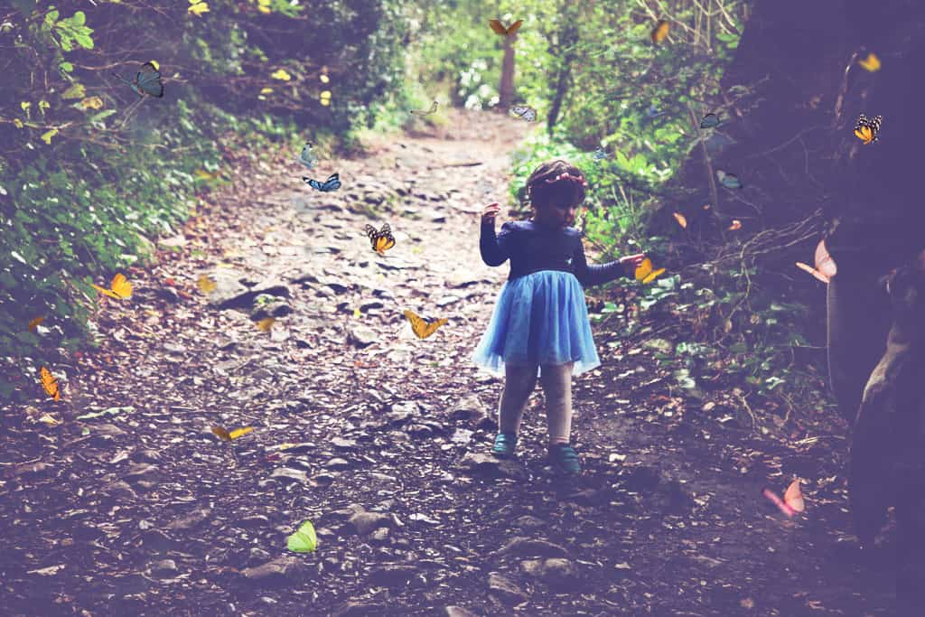 Little girl surrounded by butterflies in the woods