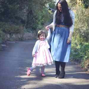 Little girl and mum wearing girly dresses and holding hands.