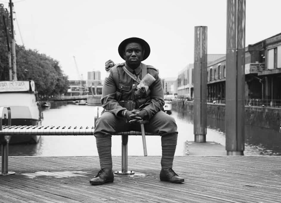 A young man dressed as a soldier to commemorate the battle of the Somme sits silently on a bench on Bristol's waterfront