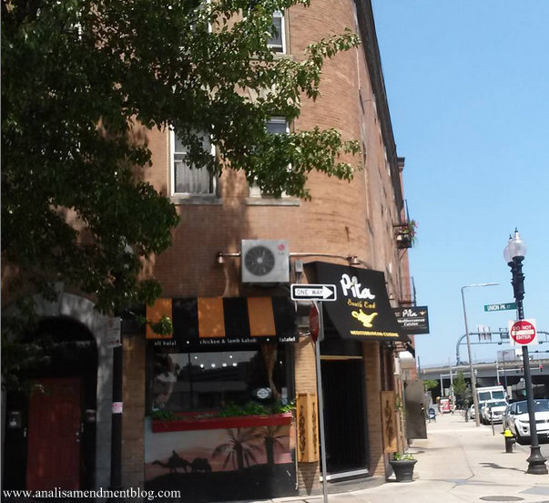 Picture of the front door, signage and street of Pita, a restaurant located in the South End area of Boston, that sells falafel.
