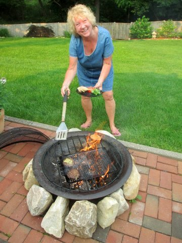 PR Consultant Chris Lyons in front of an outside fire pit grilling food.