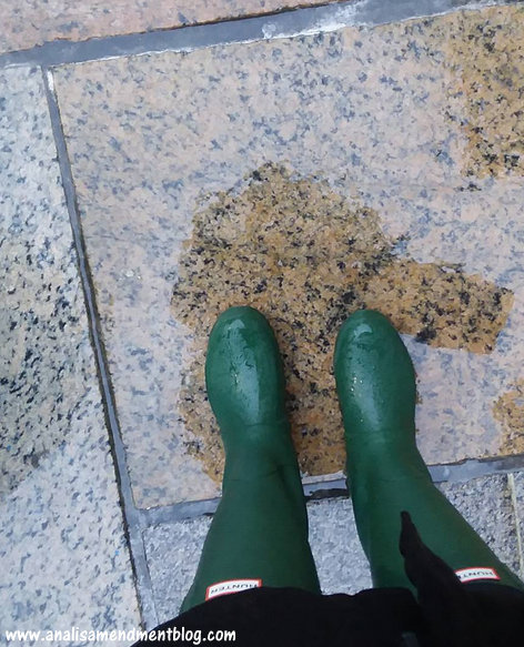 Person wearing green Hunter rain boots standing on rain soaked walkway.