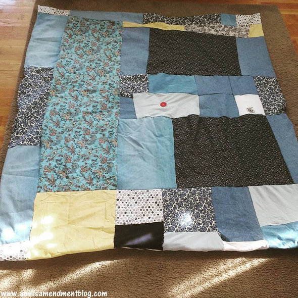 Quilt spread out on rug, patches of blue denim, along with other prints and textures.