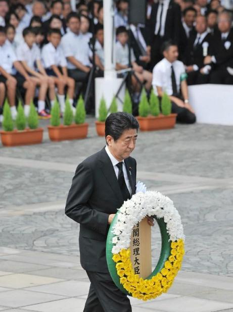 El primer ministro japonés Shinzo Abe lleva una corona de flores al altar durante la ceremonia en el Parque Memorial de la Paz en Nagasaki, a 71 años de la explosión / Foto: AFP
