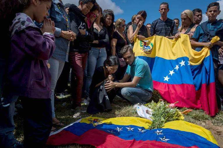 Familiares de José Díaz Pimentel y Abraham Agostini se reúnen en la parcela donde ambos fueron enterrados hoy, sábado 20 de enero del 2018, en Caracas (Venezuela)/ Foto: EFE