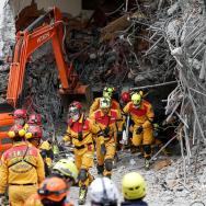 Varios miembros de los servicios de rescate salen de un edificio en ruinas durante una réplica del terremoto en Hualien, en el este de Taiwán/ Foto: EFE
