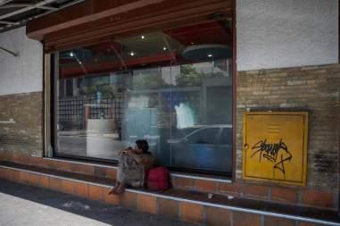 Fotografía del 3 de marzo de 2018 de un adolescente en la entrada de una panadería en Caracas (Venezuela). Foto EFE