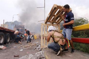 Manifestantes se protegen del ataque policial/Foto: EFE