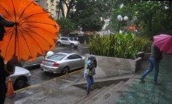 Los venezolanos se cubren de la lluvia como pueden / Foto: Lisandro Casaña
