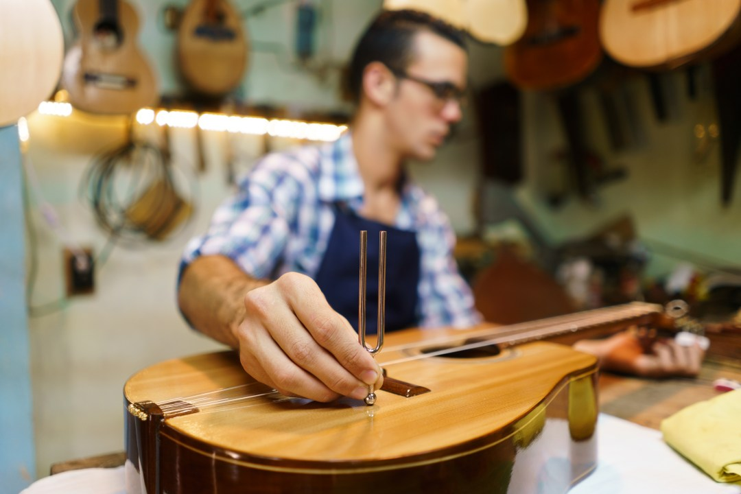 a guy tuning a guitar