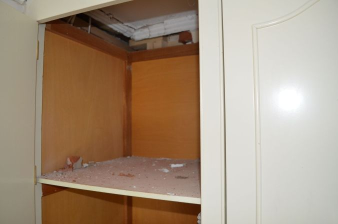 Broken brick and dust sitting in upper section of wardrobe