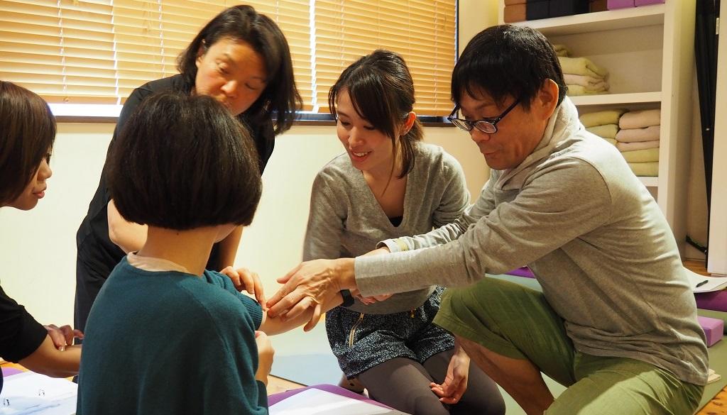 内田先生が生徒さんの腕のツボを押している