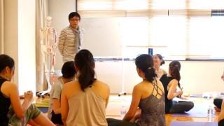 内田かつのり先生のヨガ解剖学講座「怪我をしない、させない」のクラス風景。ホワイトボードを背に立つ内田先生と取り囲む生徒さんの様子