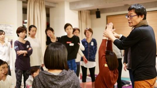 内田かつのり先生のヨガ解剖学講座の様子。生徒さんの腕を上にあげて説明している様子