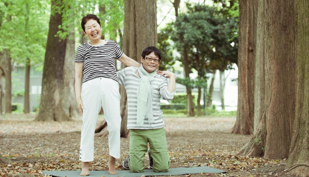 内田かつのり先生と60代女性が、森の中で笑顔で正面を向いている様子