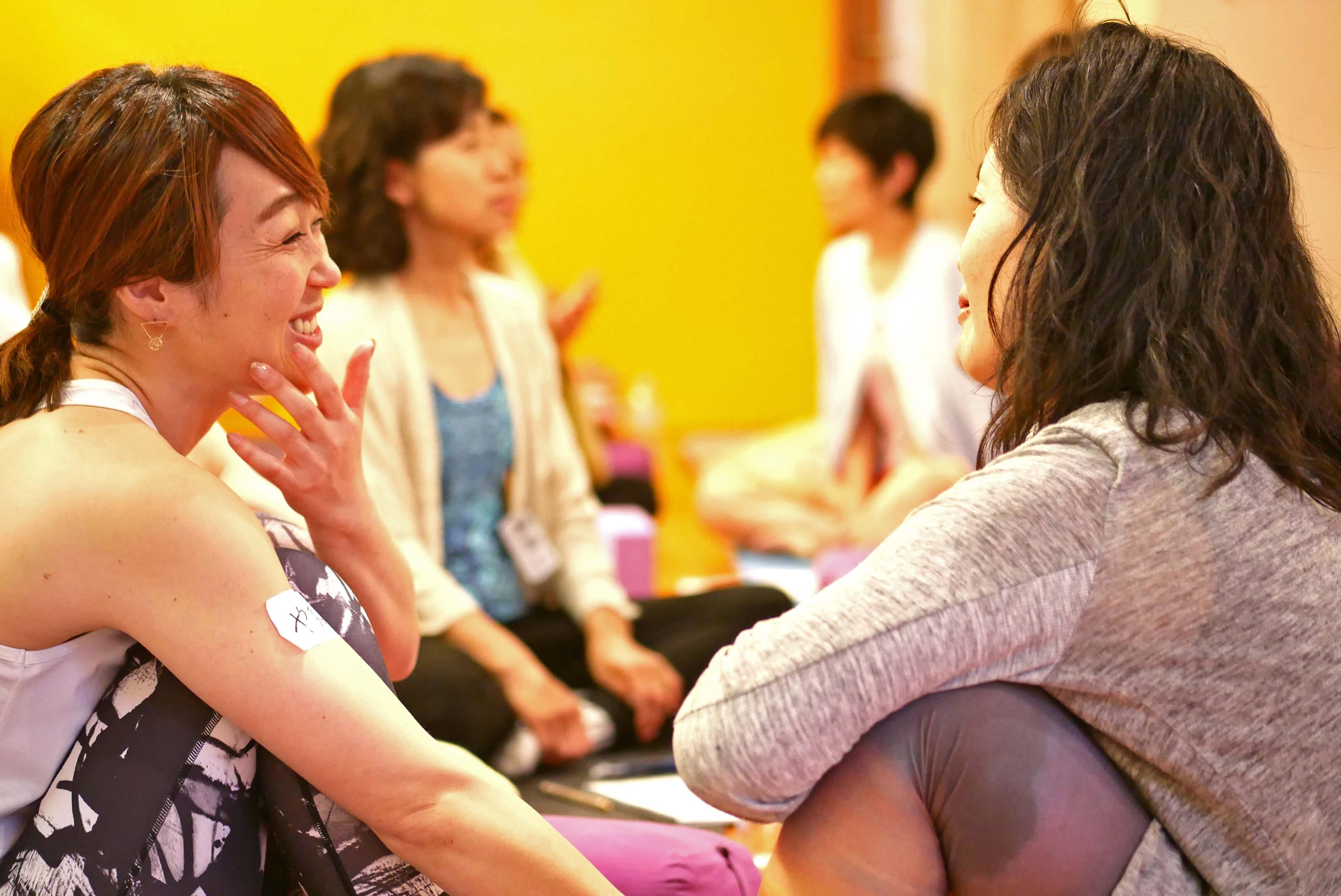 内田かつのり先生のシニアヨガ指導者養成講座の様子。生徒さん二人が笑顔でお話している様子