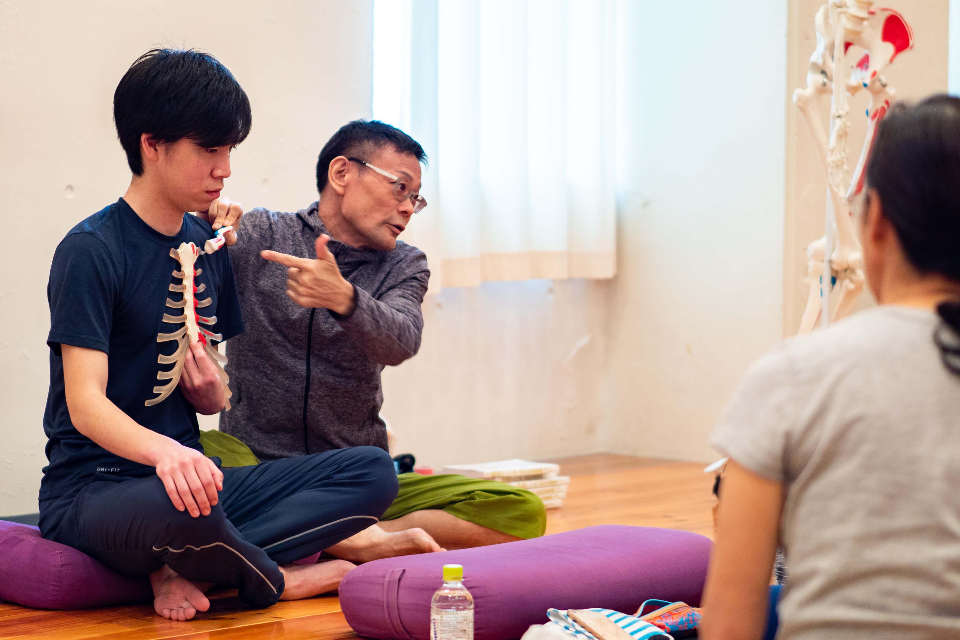 ヨガ解剖学講師内田かつのり先生のヨガ解剖学講座基礎編の様子。生徒さんをモデルにして説明する内田先生
